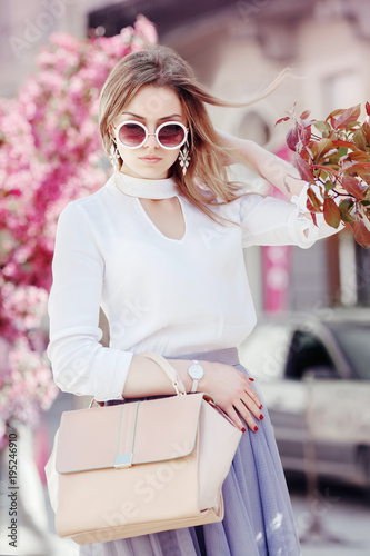Outdoor waist up portrait of young beautiful girl posing in street. Model wearing stylish round sunglasses, white shirt, wrist watch, holding pink bag, handbag. City lifestyle. Female fashion concept Wall mural
