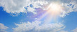 canvas print picture - Miraculous Heavenly Light Panorama Banner -  Wide blue sky, fluffy clouds and a beautiful warm orange yellow sun beaming down radiating depicting a holy entity