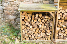 Outdoor Rack With Firewood Logs With Natural Stone Wall On The Background