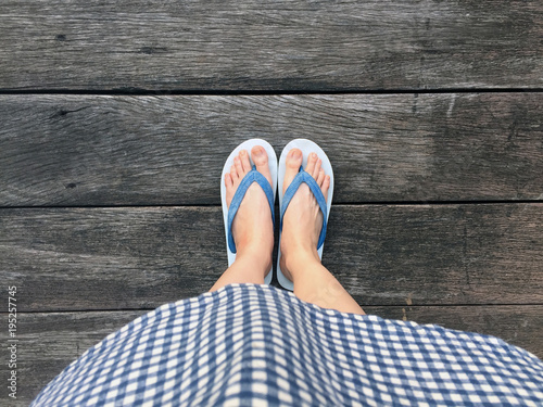 Blue Shoes Isolated on Wood Floor for Top View. Woman Wearing Blue Flip Flop and Blue Scot Dress on The Wooden Floor Background Great For Any Use.