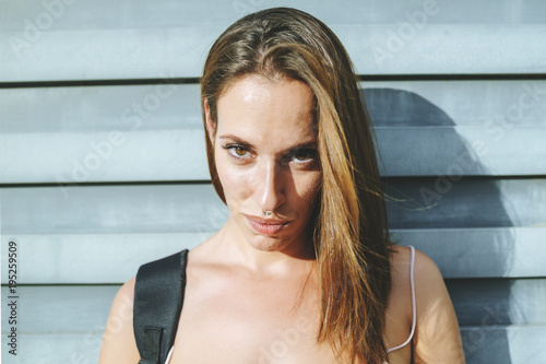 Photo  Portrait of woman with metal door in the background