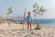 Caucasian little boy on sandy beach with tree stick