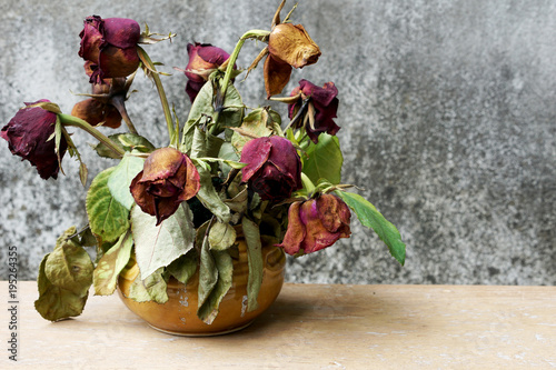 Dry roses in a vest on wooden table with old stain background, selective focus Tablou Canvas