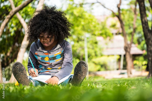 Foto  A little boy writing on notebook while sitting on green grass in a park