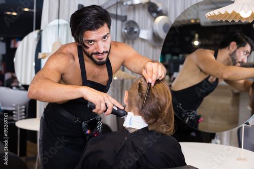 Spoed Foto op Canvas Kapsalon Cheerful male professional shaving female's hair