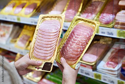 Woman chooses slice of ham at store