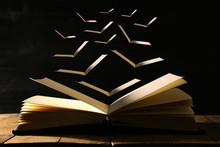 Image Of Open Antique Book Over Wooden Table With Flying Pages.