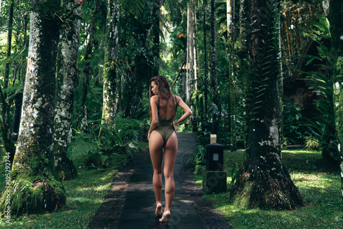 Obraz Beautiful brunette girl in green swimsuit posing in tropical location with green trees. Young sports model in bikini with perfect sexy body with long hair - fototapety do salonu