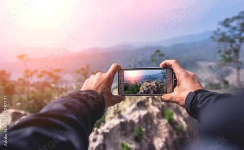 Obraz Man using smart phone take a photo mountain view - fototapety do salonu