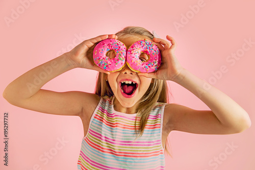 young beautiful happy and excited blond girl 8 or 9 years old holding two donuts on her eyes looking through them playing cheerful