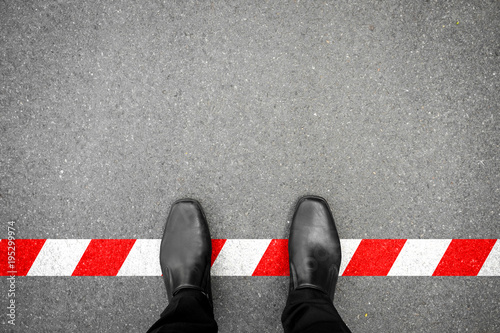 Black shoes standing on the red-white line Canvas Print