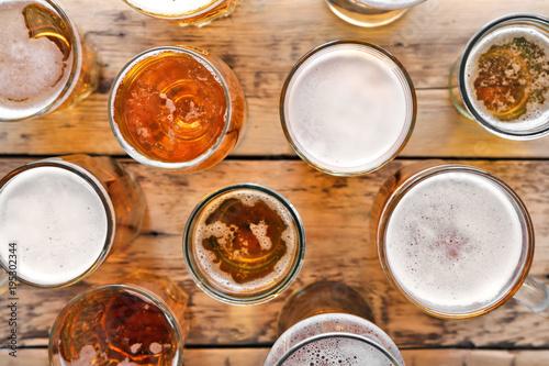 Vászonkép  Glassware with fresh beer on wooden background, top view