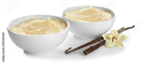 Photo Tasty vanilla pudding in dishes and sticks with flower on white background