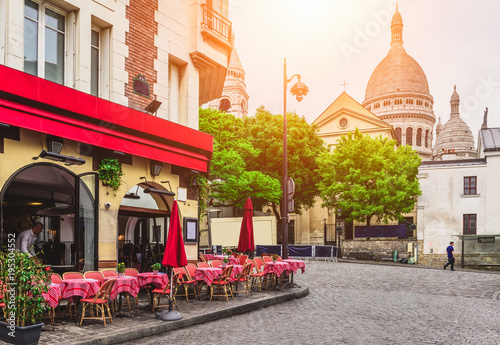 Fotobehang Parijs Cozy street with tables of cafe in quarter Montmartre in Paris, France