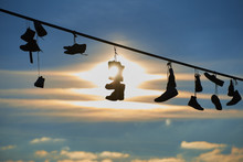 Old Shoes Hanging On Electrical Wire Against A Sky. Shoe Tossing