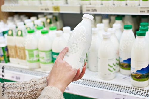 Woman chooses milk and dairy products at store