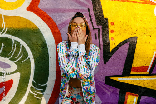 Poster Graffiti Attractive stylish girl covering her mouth by hands, looking at camera, wearing bright sportive suit and cap. Standing against the wall with graffiti.