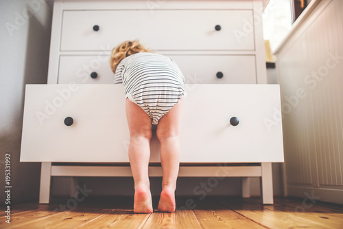 Valokuva  Toddler boy in a dangerous situation at home.