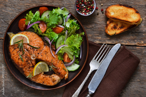 Poster Plat cuisine Salmon steak baked with Provencal herbs with garnish of vegetable salad on rustic, wooden stew.