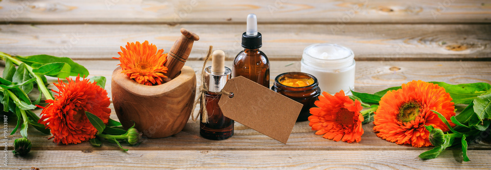 Fototapety, obrazy: Calendula aromatherapy. Essential oil and cosmetics, blank tag, banner. Wooden table background