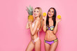 Leinwanddruck Bild Portrait of pretty, charming, laughing, stylish trendy ladies, tourists with modern hairstyle in swimsuit showing ananas and orange in hands, standing over pink background, brunette vs blonde