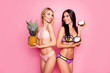 Leinwanddruck Bild Portrait of pretty, charming, hot, pretty trendy ladies, tourists with modern hairstyle in swim suit having ananas and coconut in hands, standing over pink background, looking to each other