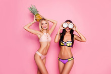 Portrait Of Hot, Charming, Stylish, Pretty, Trendy, Crazy Ladies, Tourists In Swim Suits, Blonde Having Ananas On Her Head, Brunette Having Coconut On Eyes' Place, Standing Over Pink Background