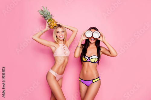 Obraz Portrait of hot, charming, stylish, pretty, trendy, crazy ladies, tourists in swim suits, blonde having ananas on her head, brunette having coconut on eyes' place, standing over pink background - fototapety do salonu