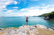 Lifestyle woman standing relax on a rock above the ocean and welcomes the sea Thailand, she is looking to the horizon and hands upwards, background the sea waves summer. Vacation and Travel Concept