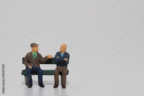 Photo miniatura di anziani seduti su una panchina mentre parlano