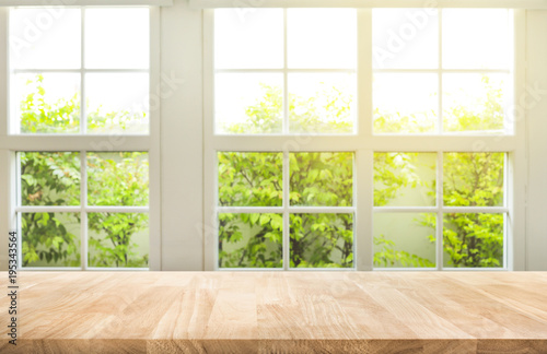 Fotografia Top of wood table counter on blur window view garden background.