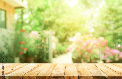 Empty wood table top on blur abstract green from garden and house background