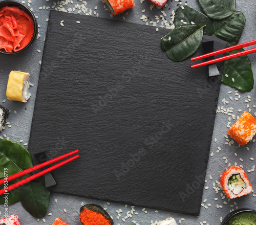 Square black slate with sushi on grey background