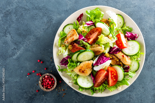 Obraz Fresh vegetable salad of tomatoes, cucumbers, italian mix, lettuce and grilled chicken breast - fototapety do salonu