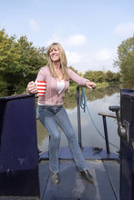 Woman Holding A Mug And Using The Tiller To Steer A Narrowboat Along A Canal In The UK