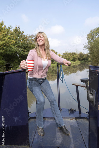 Leinwand Poster Woman holding a mug and using the tiller to steer a narrowboat along a canal in