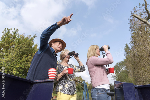 Fotografia, Obraz Group of people on a boating holiday using binoculars to spot wildlife along the