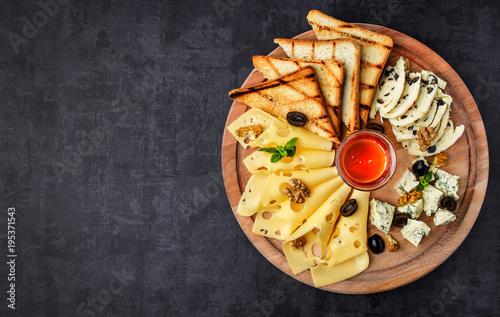 Plakat Płyta serowa: parmezan, cheddar, gouda, mozzarella i inne z bazylią na desce na ciemnym tle z miejscem na tekst. Miód i krakersy