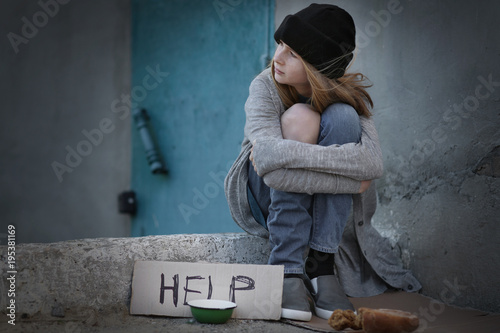 Fényképezés  Homeless poor teenage girl sitting outdoors near empty bowl and piece of cardboa