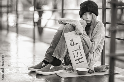 Fotografija  Homeless poor teenage girl holding piece of cardboard with word HELP outdoors