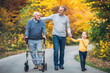 canvas print picture - Elderly father adult son and grandson out for a walk in the park.