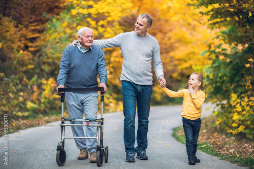 Fotografiet Elderly father adult son and grandson out for a walk in the park.