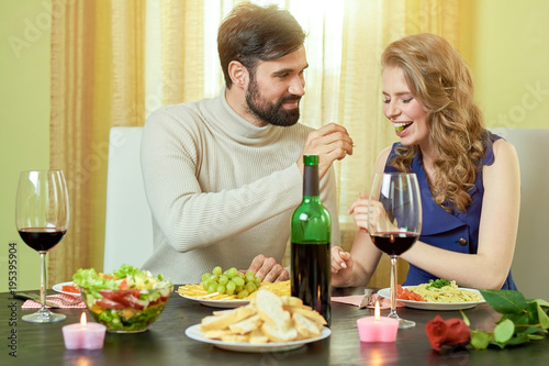 guy feeding grape to girl young couple romantic dinner stay at
