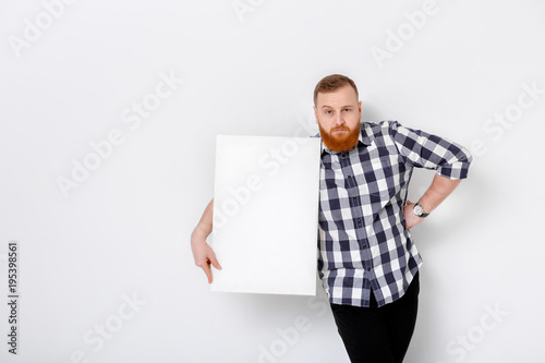 man with beard holding big white card.