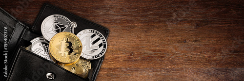 Fototapeta crypto currency coin in leather wallet on wide wood wooden panorama background with copy space bitcoin ethereum litecoin iota ripple obraz