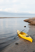 Vertical Photo Of Yellow Kayak And Paddle On A Beach.