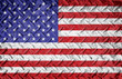 Rough textured metal diamond plate background with american flag layered. Red white and blue american old glory flag.