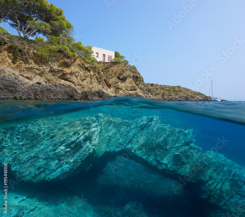 Papiers peints Cote Rocky coast with a small house and a natural rock formation underwater in the Mediterranean sea, split view above and below water surface, Catalonia, Cap de Creus, Costa Brava, Spain