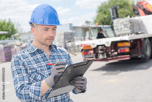 Valokuvatapetti Man in builders yard holding clipboard