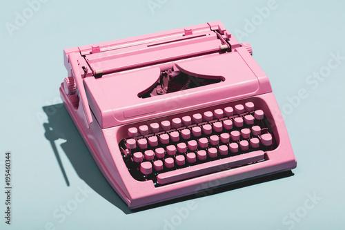 Pink typewriter on a blue pastel background.